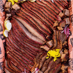 Sliced hot and fast brisket on Hey Grill Hey peach butcher paper.