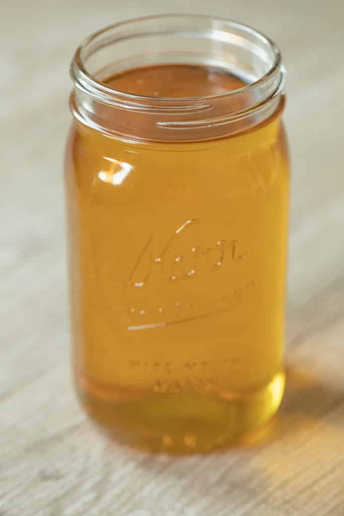 Glass mason jar of rendered and strained beef fat.