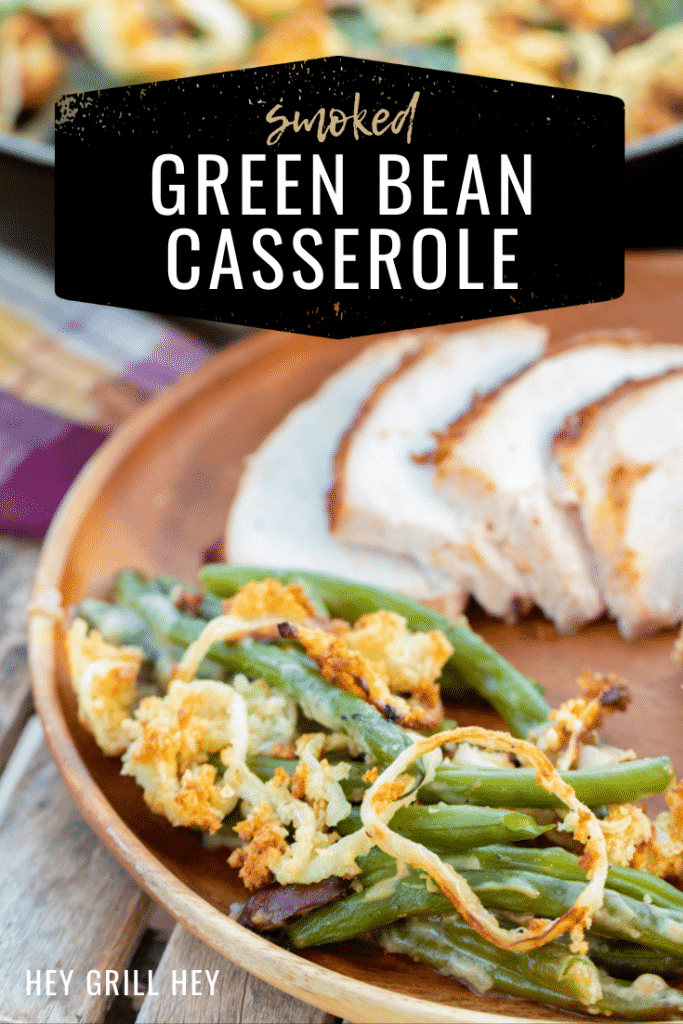 "Green bean casserole on a plate next to sliced meat. Text overlay reads, ""Smoked Green Bean Casserole."""