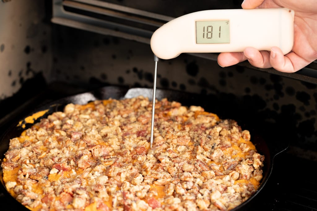 Peach colored instant read thermometer stuck in a sweet potato casserole reading 181 degrees F.