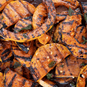 Grilled butternut squash slices stacked on a plate.