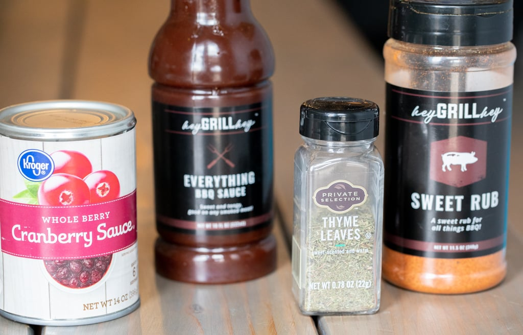 A can of cranberry sauce, a bottle of Everything Sauce, thyme leaves, and a bottle of sweet rub on a table.
