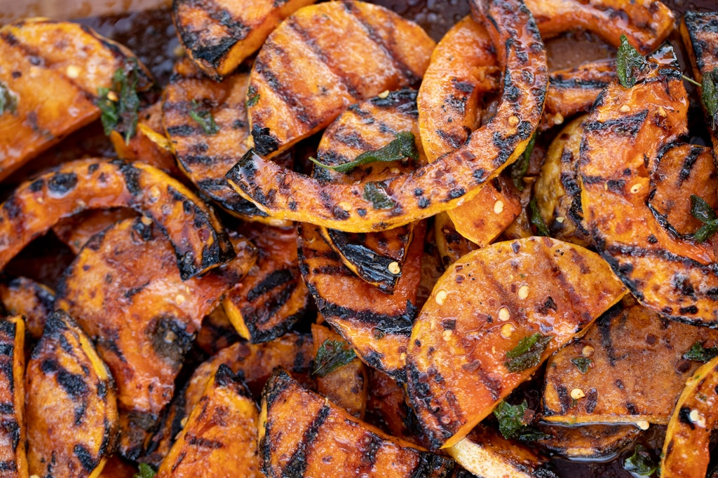 Grilled butternut squash slices in a pile.