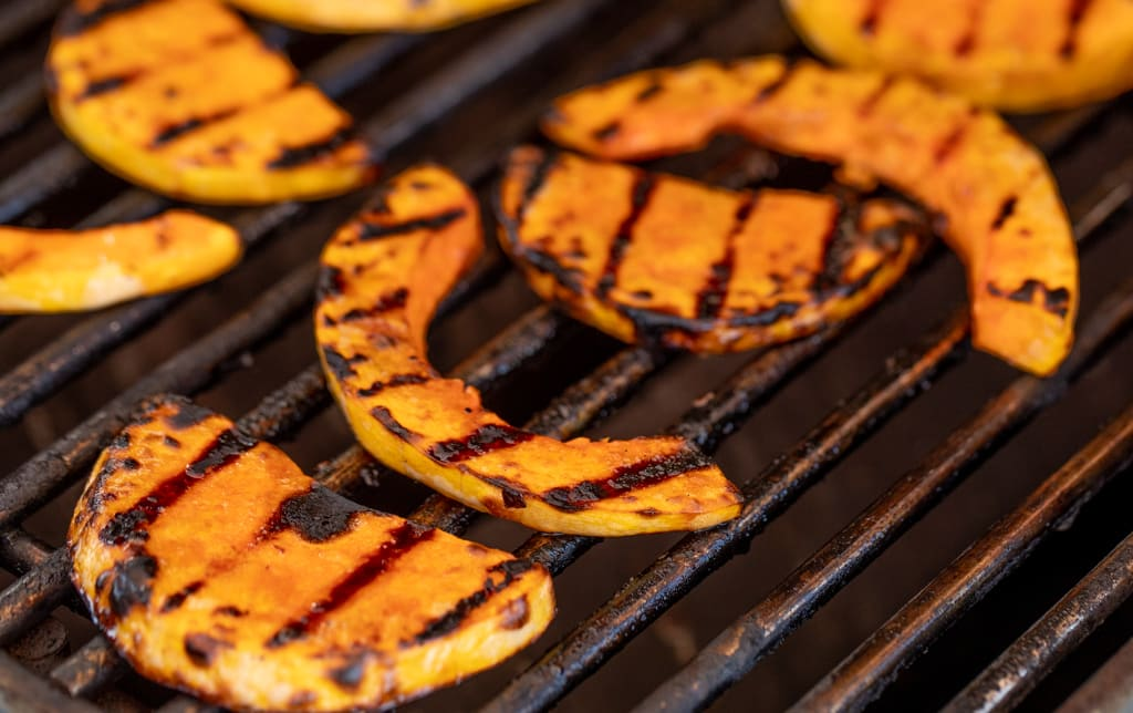 Sliced butternut squash with grill marks, while still on the grill.