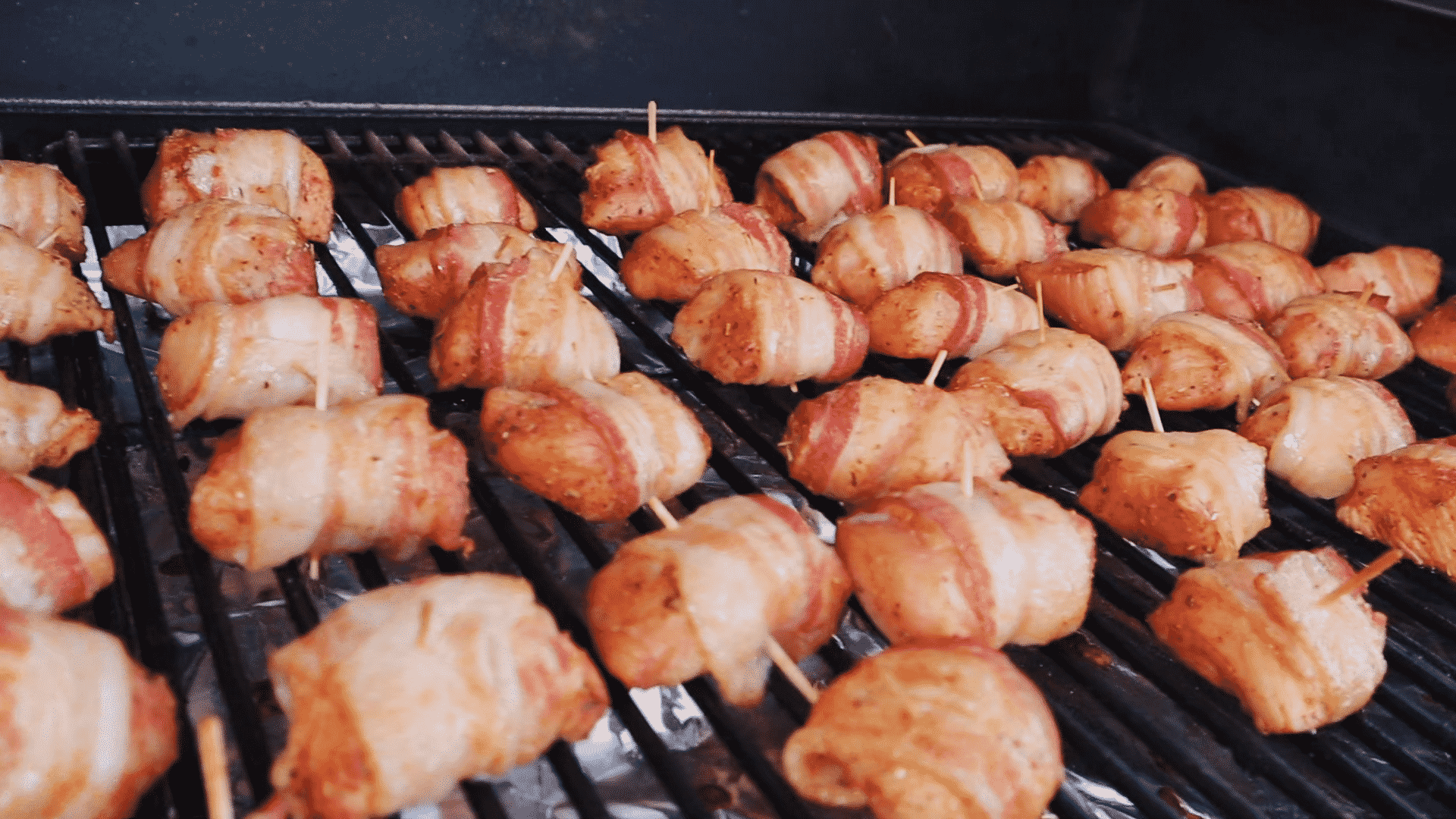 Bacon wrapped turkey bites lined up on the grill grates of a smoker.