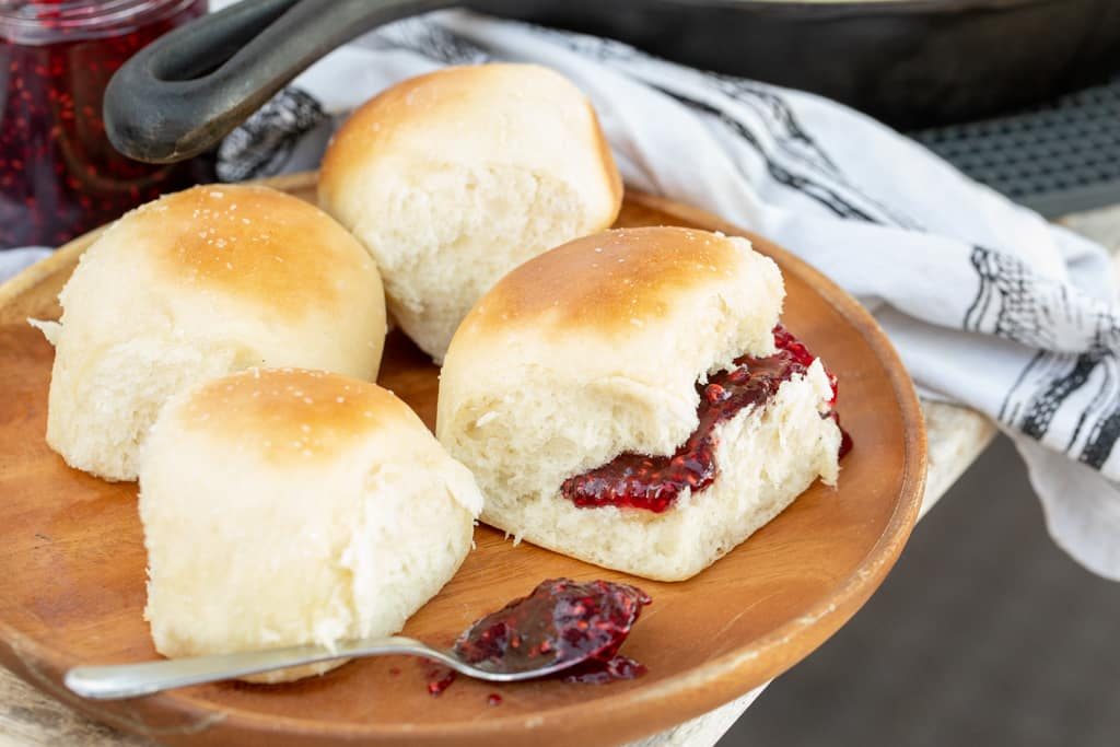 4 separated cooked rolls on a wooden plate and one roll has raspberry jam spread inside.