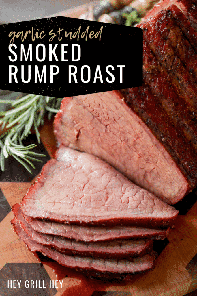 Smoked and sliced beef rump roast on a wooden cutting board next to fresh herbs and metal utensils. Text overlay reads: Garlic Studded Smoked Rump Roast.