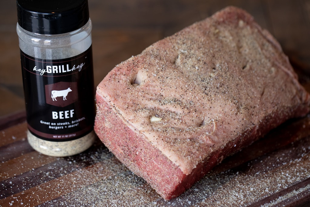 Whole uncooked rump roast inserted with garlic cloves and seasoned with Hey Grill Hey Beef Seasoning next to a bottle of Beef Seasoning.