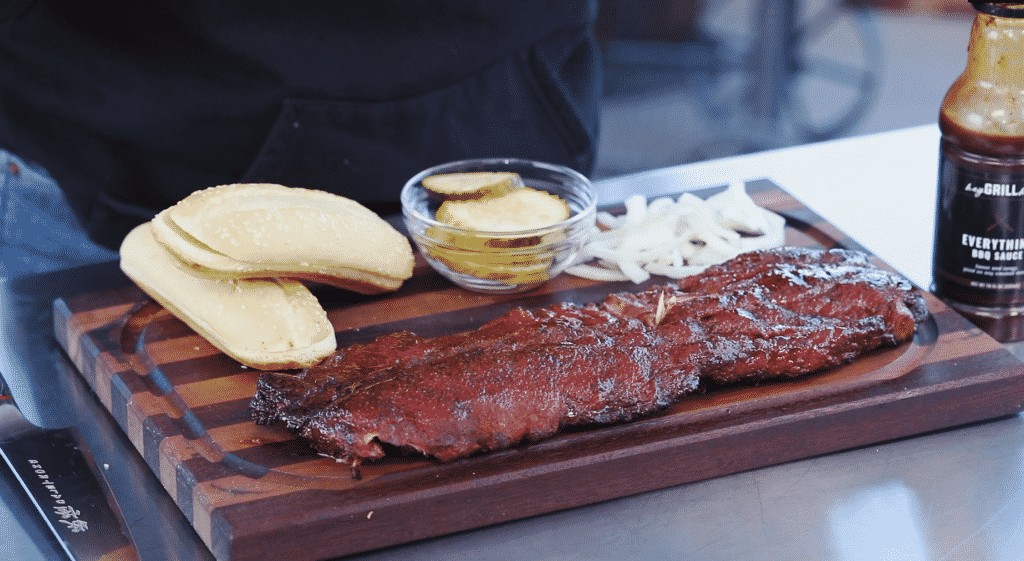 Rack of smoked pork ribs, two sandwich buns, sliced white onion, and sliced dill pickles on a wooden cutting board.