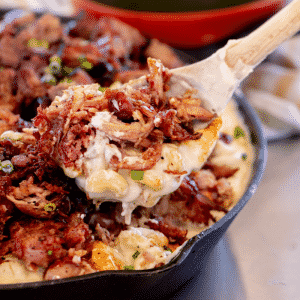 Smoked pulled pork mac and cheese being pulled out of a cast iron skillet with a wooden spoon.