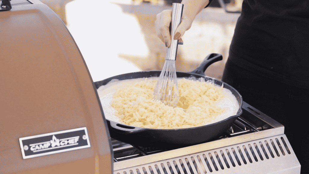 Shredded white cheddar and gouda cheese being whisked into milk and roux in a cast iron skillet.