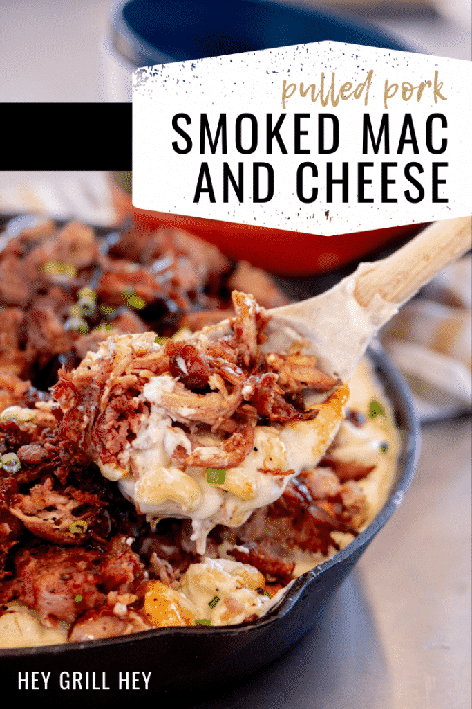 Smoked pulled pork mac and cheese being pulled out of a cast iron skillet with a wooden spoon. Text overlay reads: Pulled Pork Smoked Mac and Cheese.