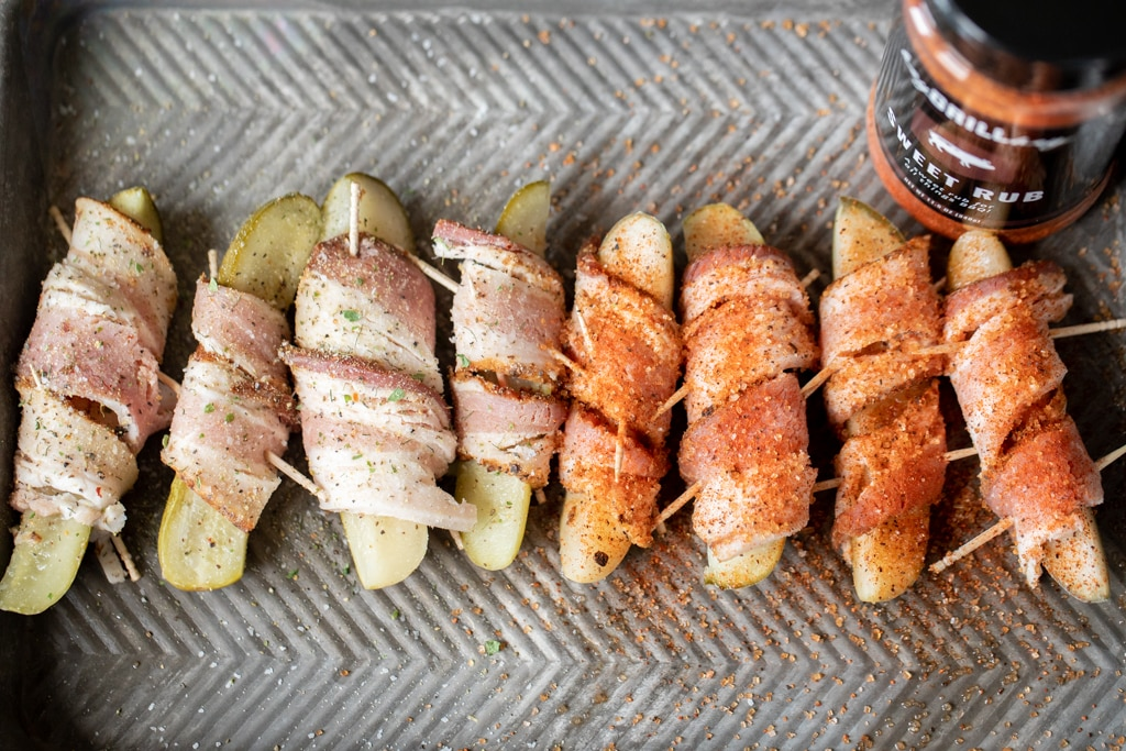 Seasoned bacon wrapped pickle spears lined up on a metal baking dish.
