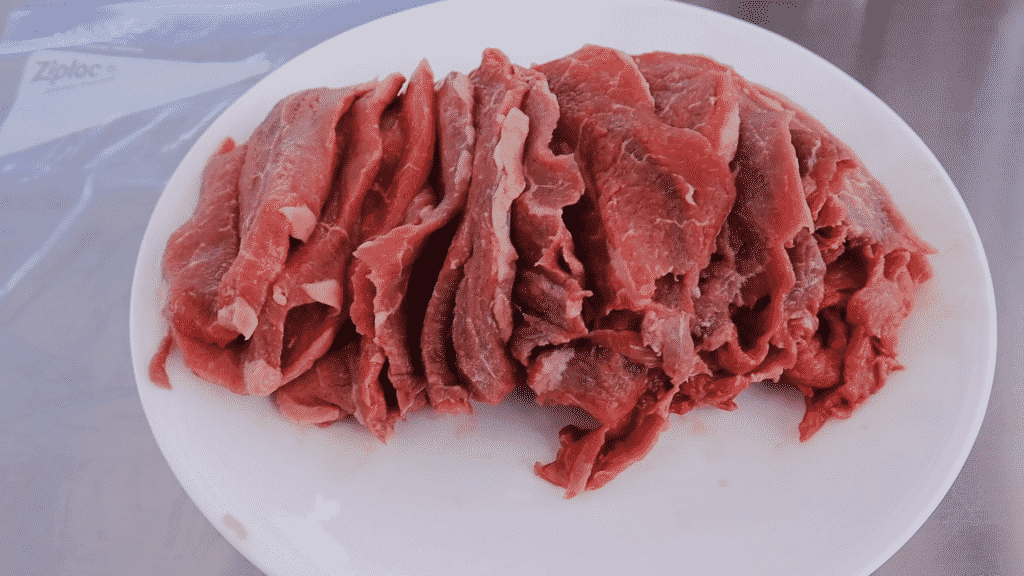 Sliced uncooked rump roast on a white plate.