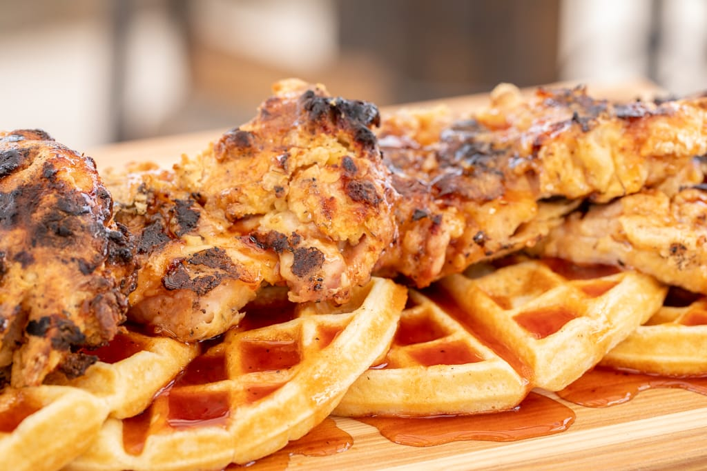 Grilled chicken breast on top of waffles on a wood cutting board glazed with sauce.