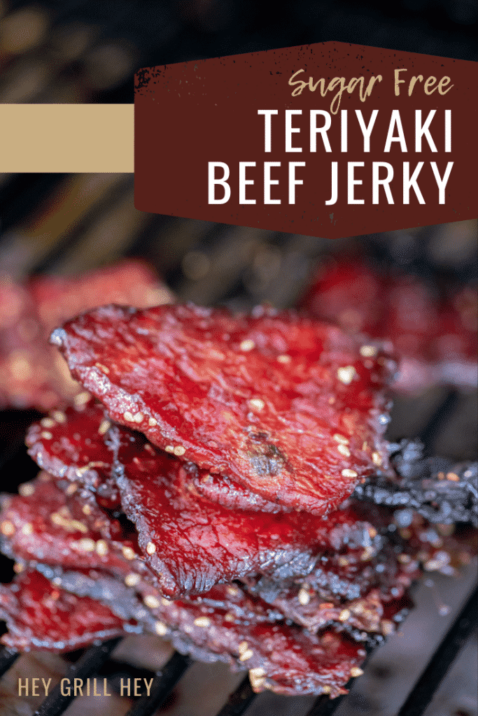 Teriyaki sugar free beef jerky stacked on the grill grates of a smoker. Text overlay reads: Sugar Free Teriyaki Beef Jerky.