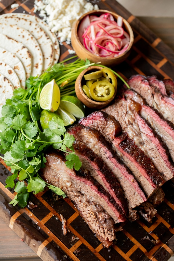 Slices of beef brisket, fresh cilantro, flour tortillas, sliced jalapenos, and a small bowl of pickled red onions arranged on a large wooden cutting board.