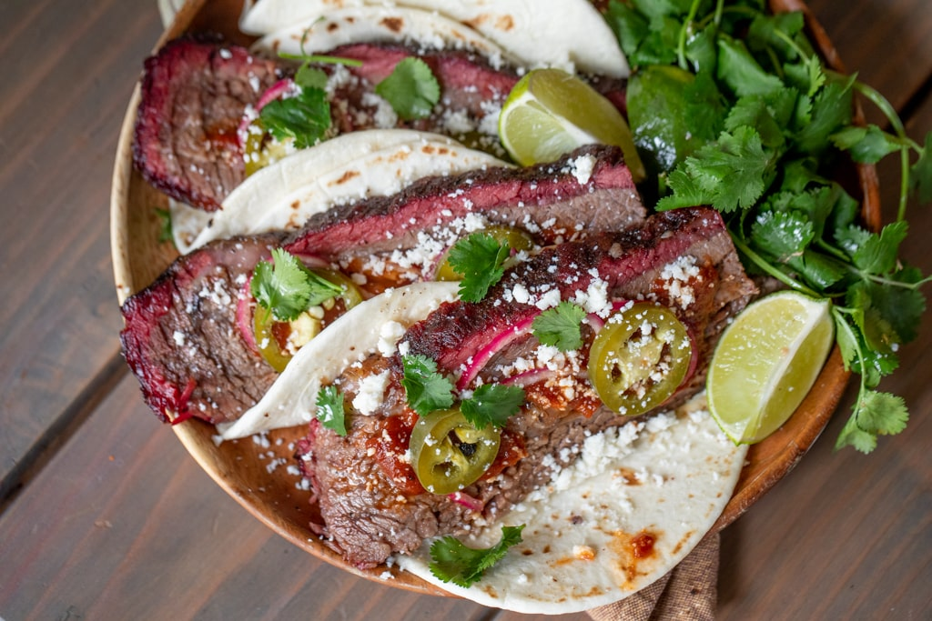 Three brisket tacos lined up on a wooden cutting board.