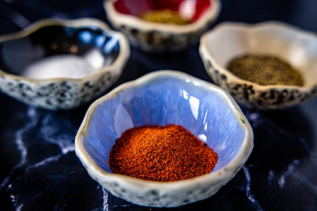 Four bowls full of ingredients for chili seasoning, including smoked paprika, salt, pepper, and seasonings.