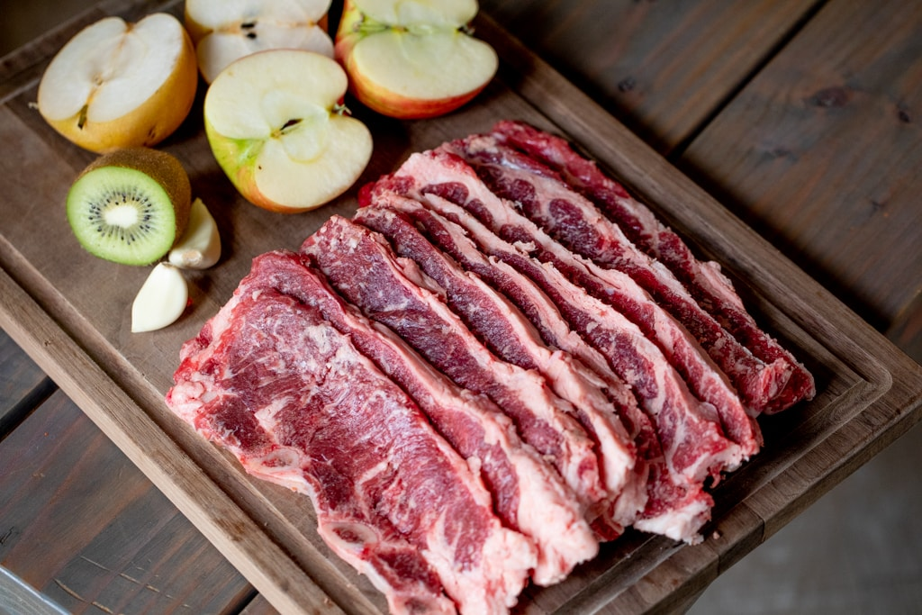 Sliced short ribs lined up on a rectangular wooden cutting board next to four apple halves and sliced kiwi.