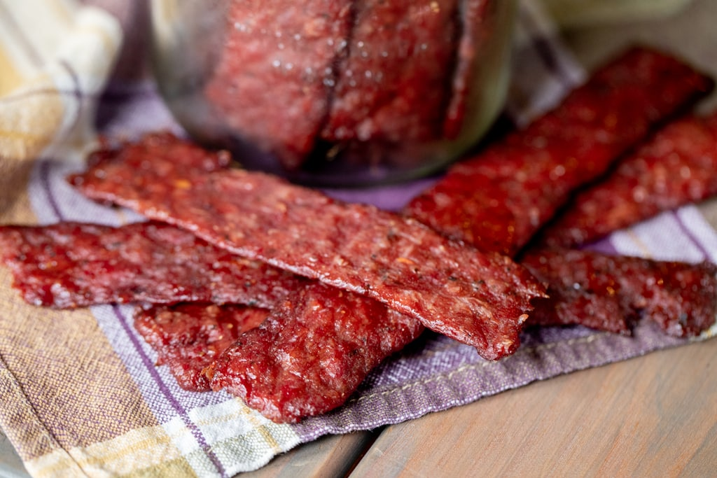 Four strips of ground beef jerky stacked on a plaid kitchen towel next to a mason jar full of ground beef jerky strips.