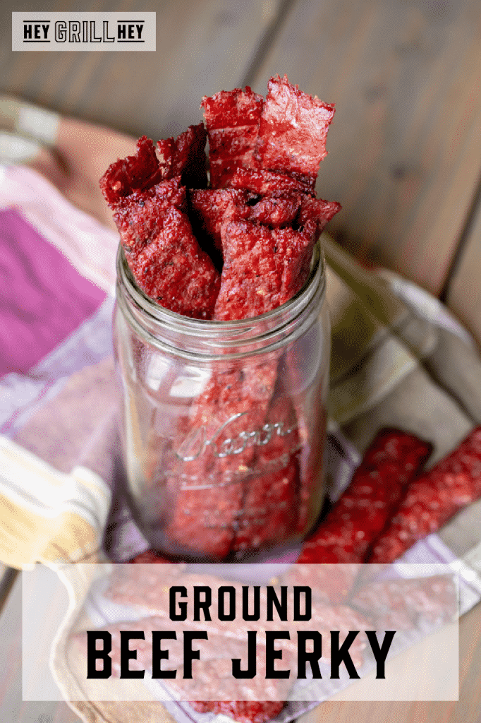 Strips of ground beef jerky in a glass mason jar on a colorful kitchen towel. Text overlay reads: Ground Beef Jerky.