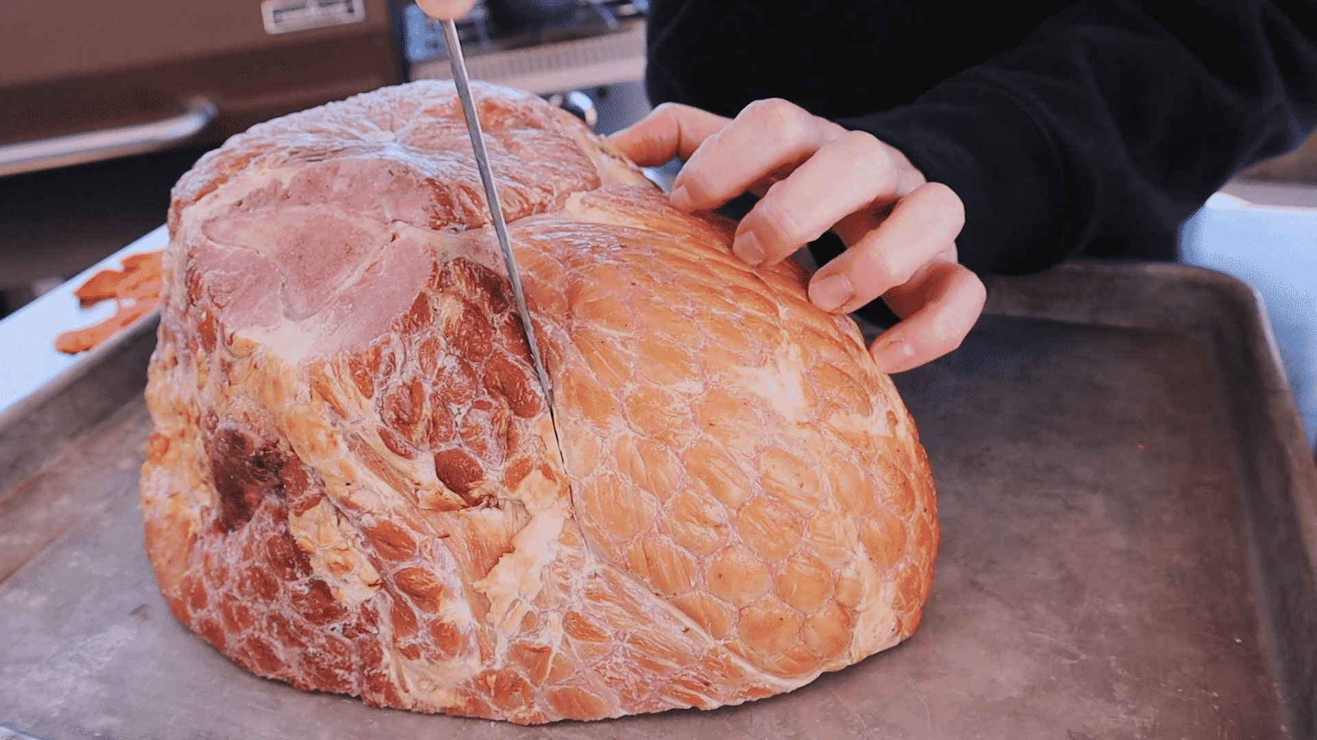 Susie uses a paring knife to make score marks across the surface of a whole picnic ham.
