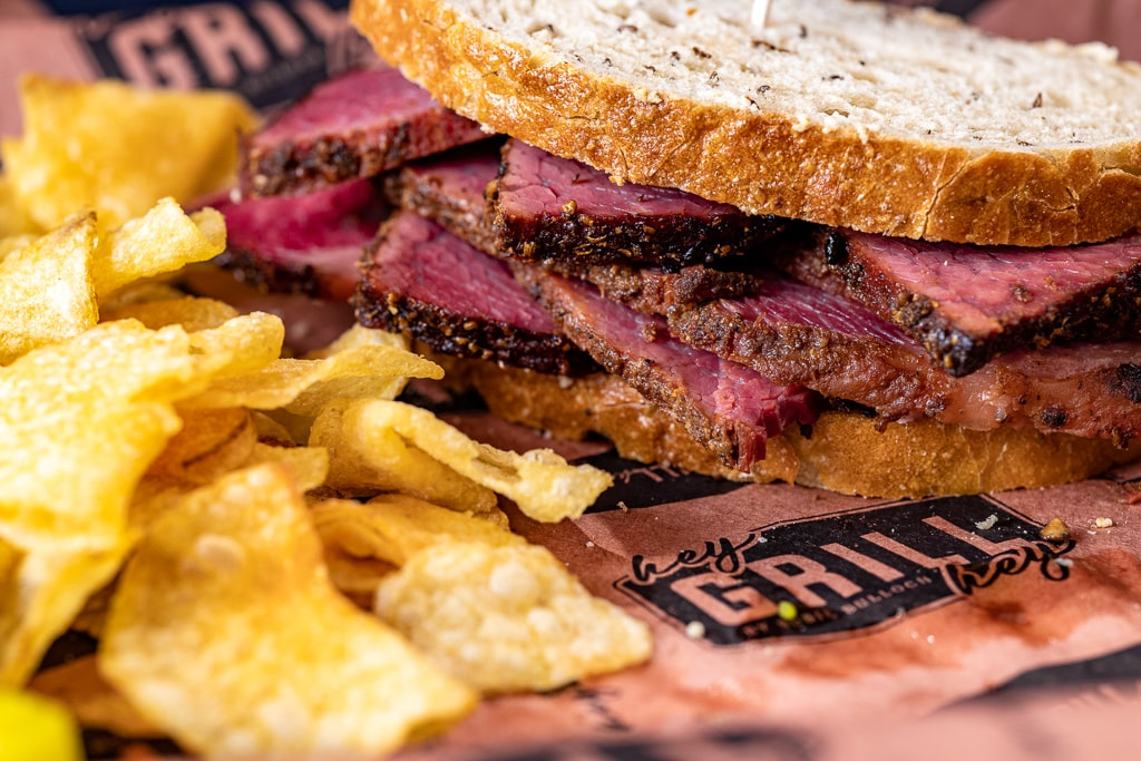 Pastrami sandwich on Hey Grill Hey butcher paper next to potato chips.