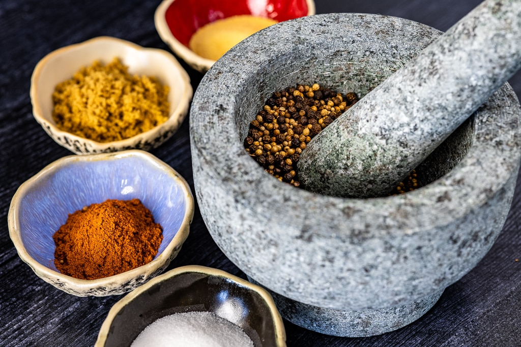 Ingredients for pastrami seasoning in small bowls with various seeds in a mortar and pestle.
