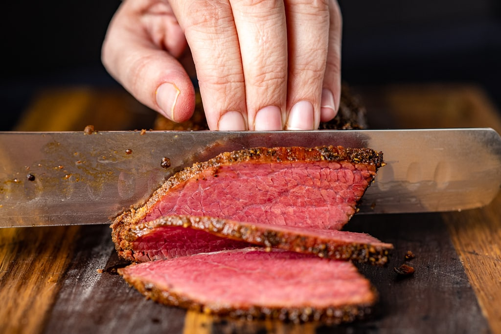 Chef knife slicing through pastrami on a wooden cutting board.