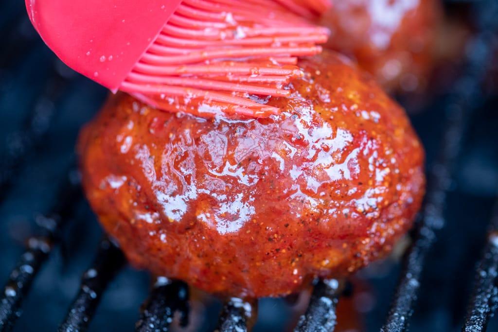 Red basting brush brushing BBQ sauce on a smoked scotch egg.