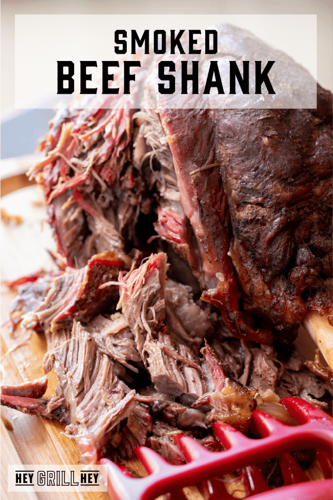 Smoked beef shank on a wooden cutting board with part of the beef shredded off the bone. Text overlay reads: Smoked Beef Shank.