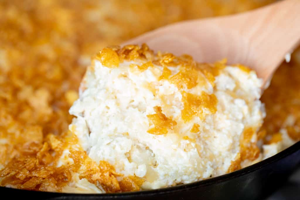 Scoop of smoked funeral potatoes on a wooden spoon.