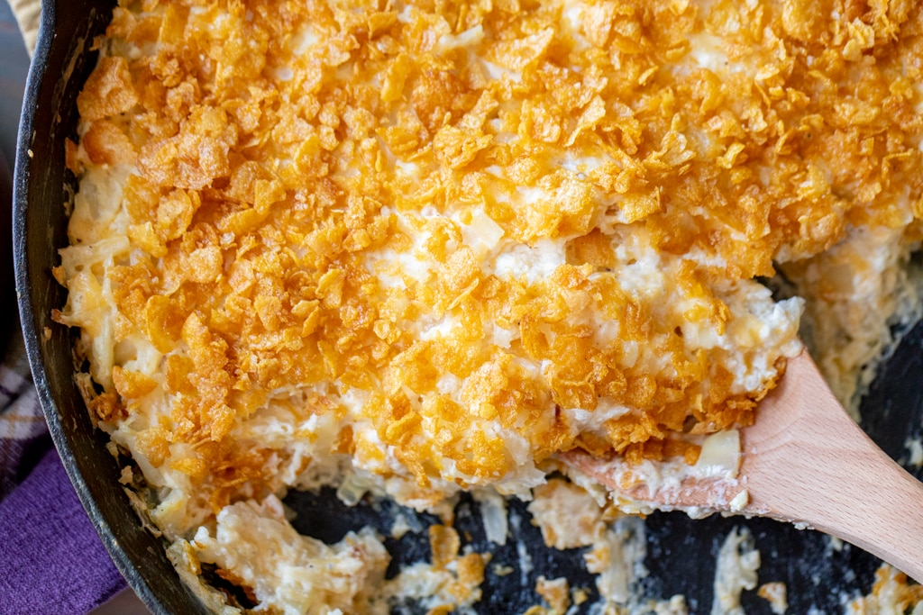Wooden spoon taking a scoop of smoked funeral potatoes out of a cast iron skillet.