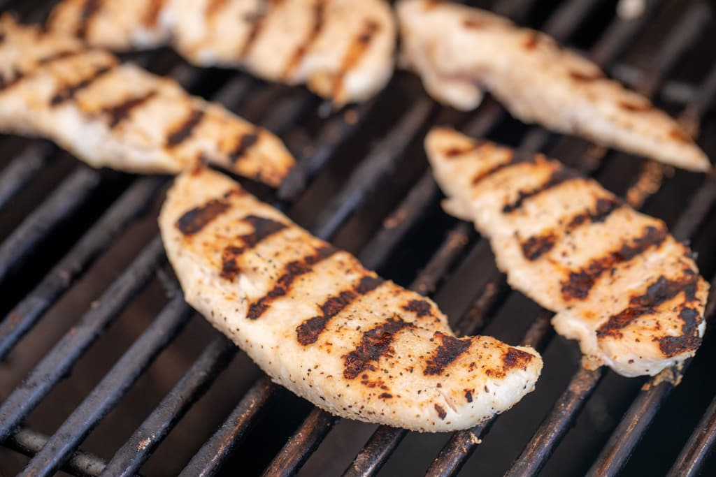 Seasoned chicken tenders on the grill grates of a grill.