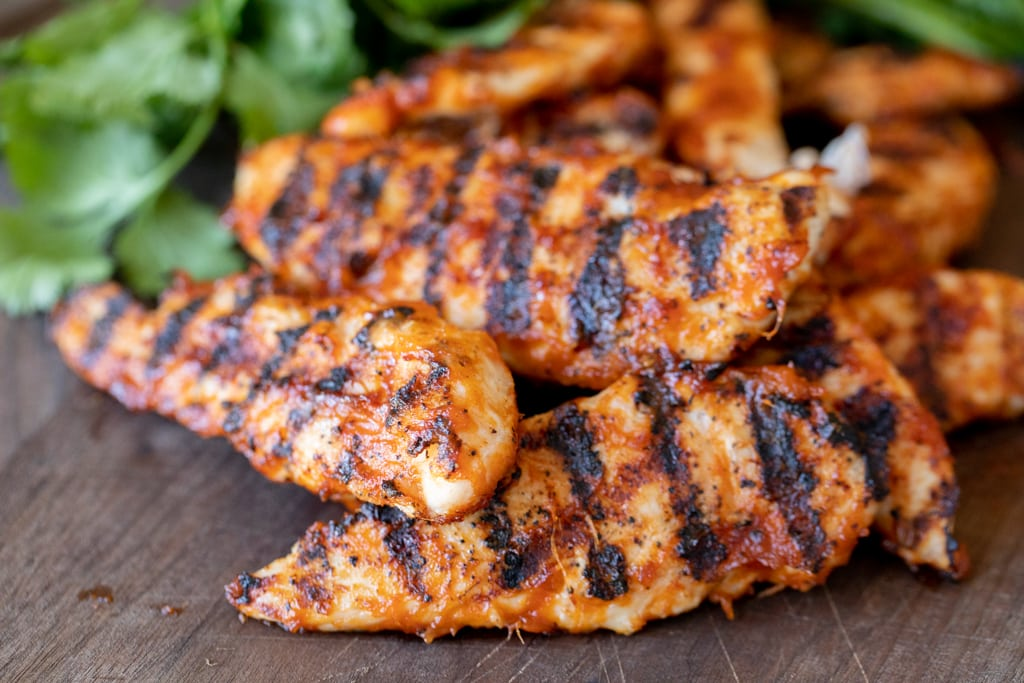 Grilled chicken tenders stacked on a wooden cutting board with fresh herbs in the background.