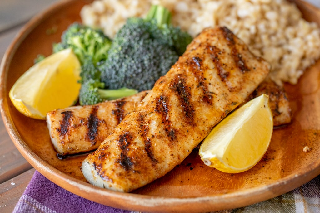 Two grilled mahi mahi filets on a wood plate surrounded by broccoli, rice, and lemon wedges.