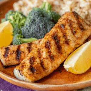 Two grilled mahi mahi filets on a plate surrounded by broccoli, rice, and lemon wedges.