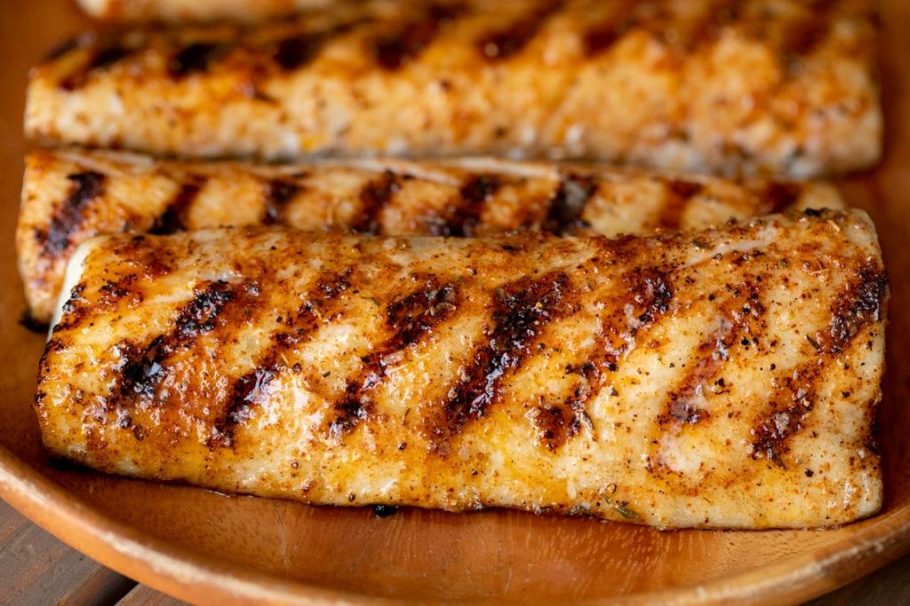 Grilled mahi mahi seasoned with homemade blackened seasoning on a wood plate.