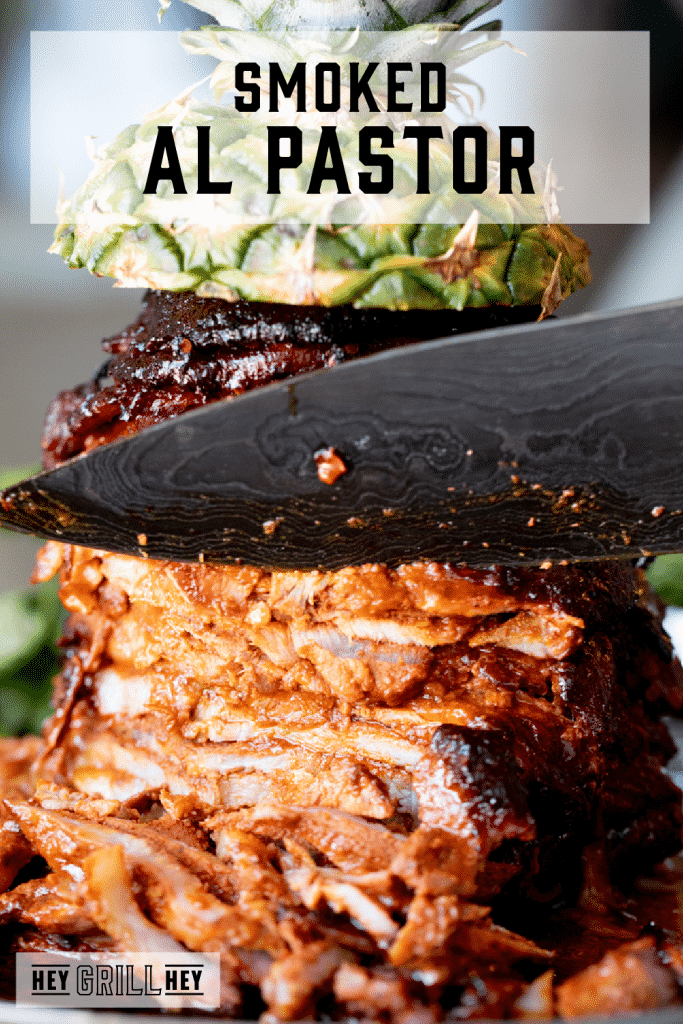 Chef's knife cutting into a stack of al pastor meat on a spit with text overlay - Smoked Al Pastor.