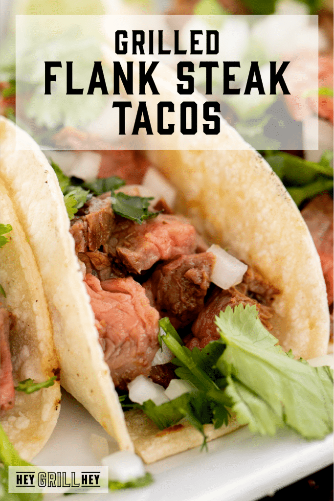 Flank steak taco on a white plate with text overlay - Grilled Flank Tacos.