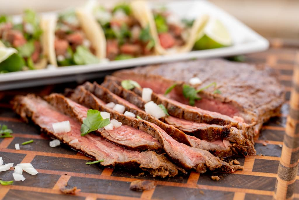 Sliced flank steak on a wooden cutting board with flank steak tacos in the background.