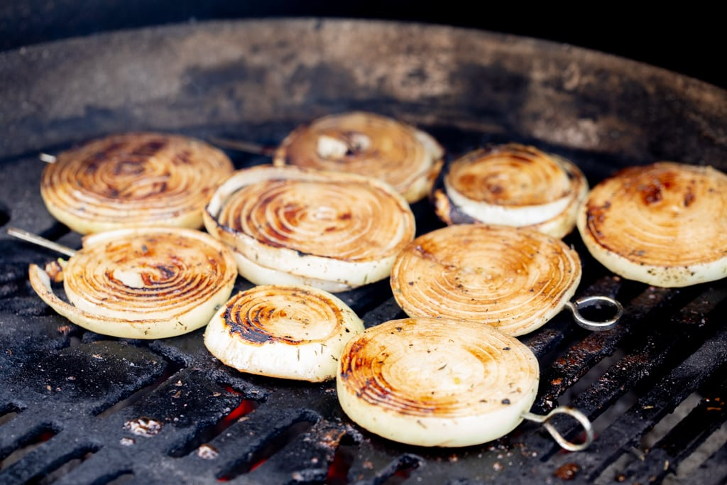 Marinated onions on the grill grates of a grill.