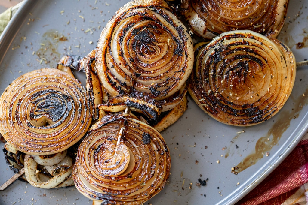Grilled onion slices on a metal baking dish.