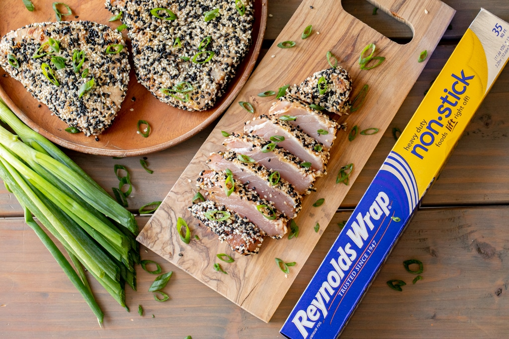 Grilled and sliced tuna steak on a wooden cutting board.