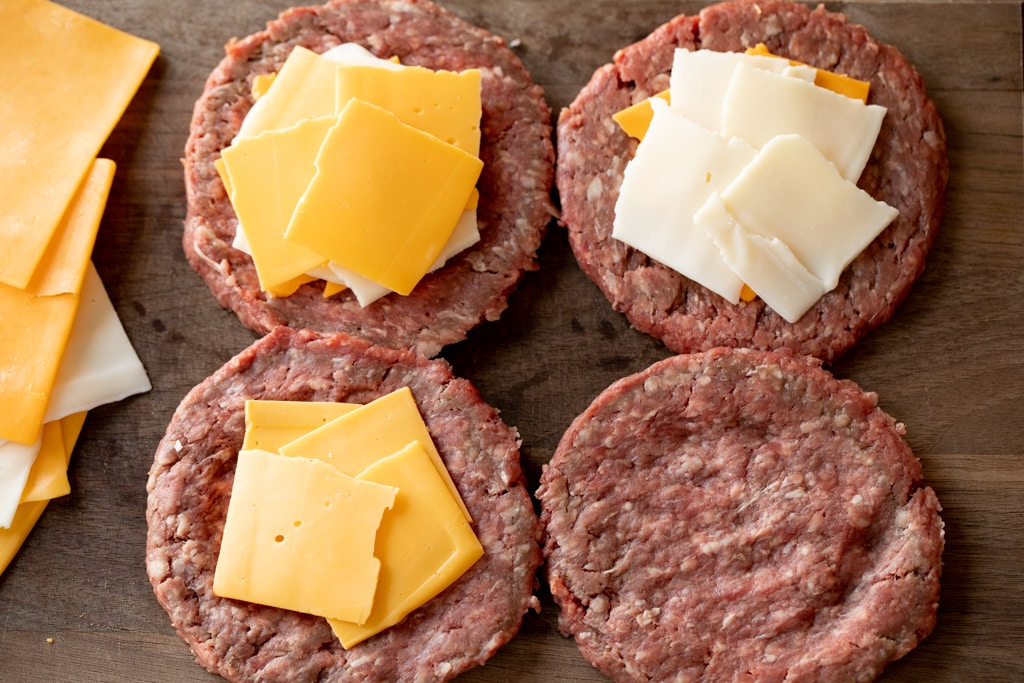 Formed burger patties covered with slices of cheese on a wood cutting board.