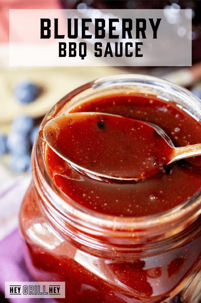 Blueberry BBQ sauce in a glass mason jar with a spoon resting on top of the jar with text overlay - Blueberry BBQ Sauce.