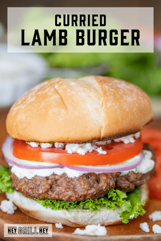 Lamb Burger topped with tomato, onion, lettuce, and feta cheese with text overlay - Grilled Lamb Burger.