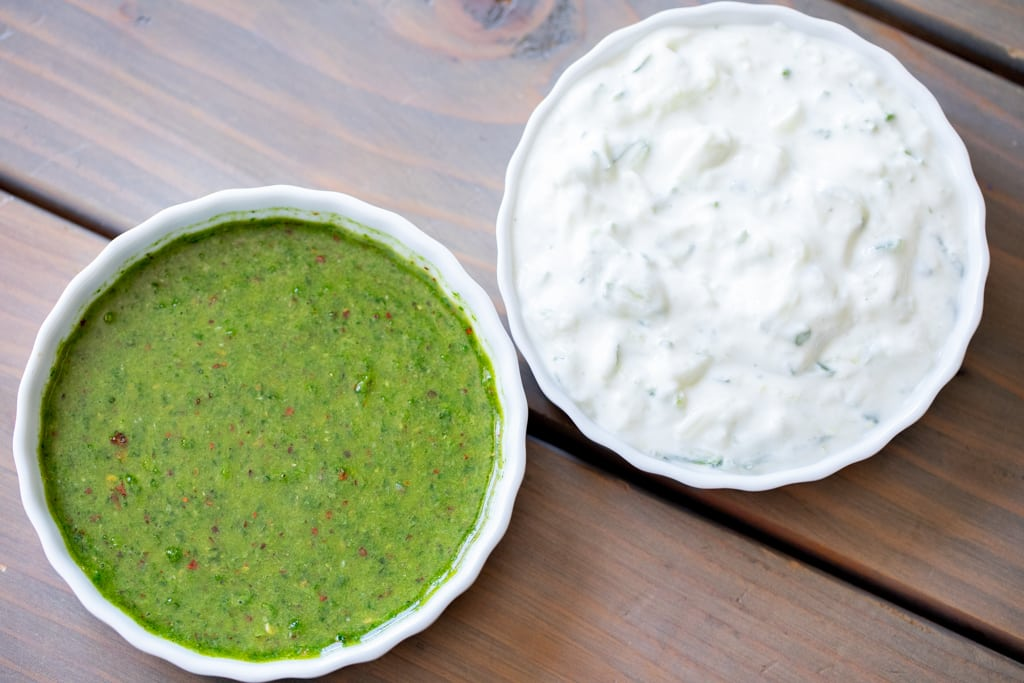Mint sauce and tzatziki sauce in white bowls.