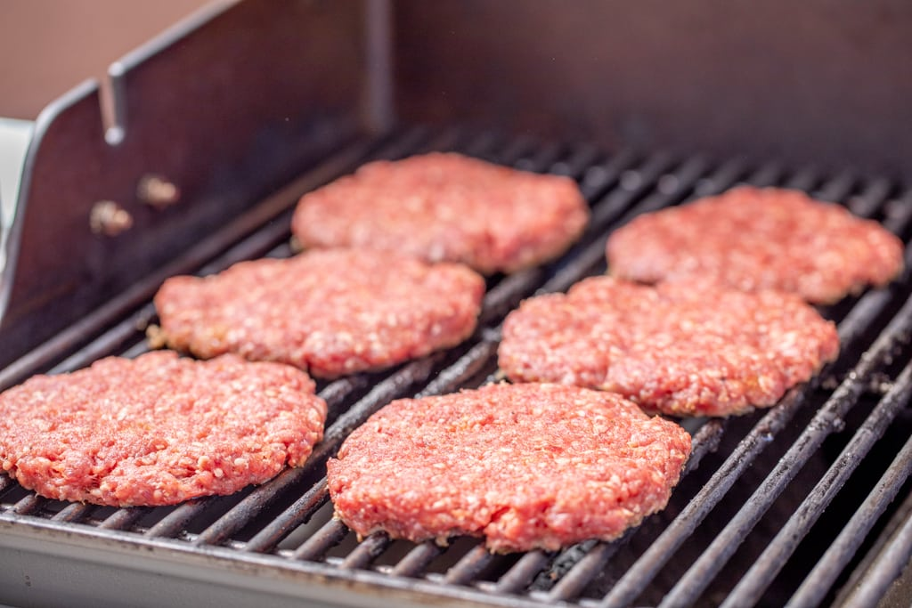 Six lamb burger patties on the grill grates of the gas grill.